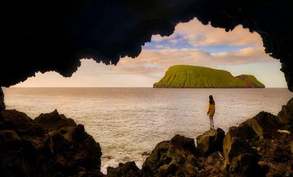 rapariga a olhar para o mar atraves de uma gruta - Ilha terceira